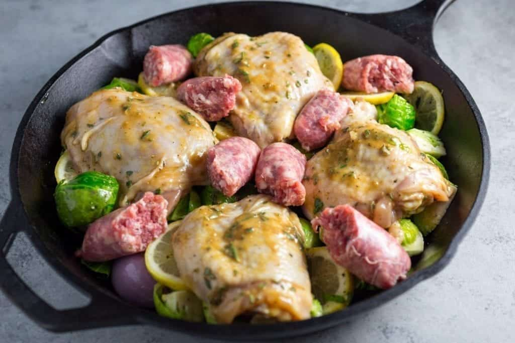 Layer the chicken and sausages on top