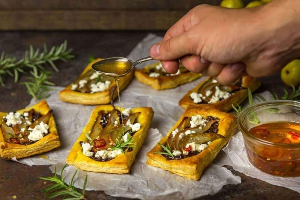 Puff Pastry Tartlets with Roasted Pear, Caramelized Red Onions, Goat Cheese and Spicy Honey Drizzle